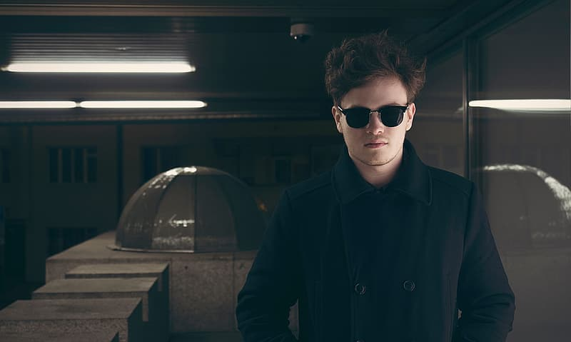 Man wearing peacoat and sunglasses
