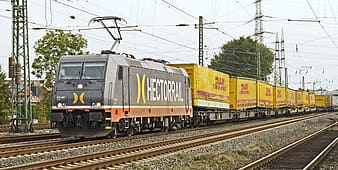 Gray and yellow Hectorral train on railway beside transfer tower