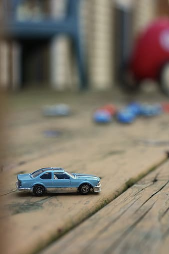 Selective focus photography of blue coupe scale model on brown wooden surface