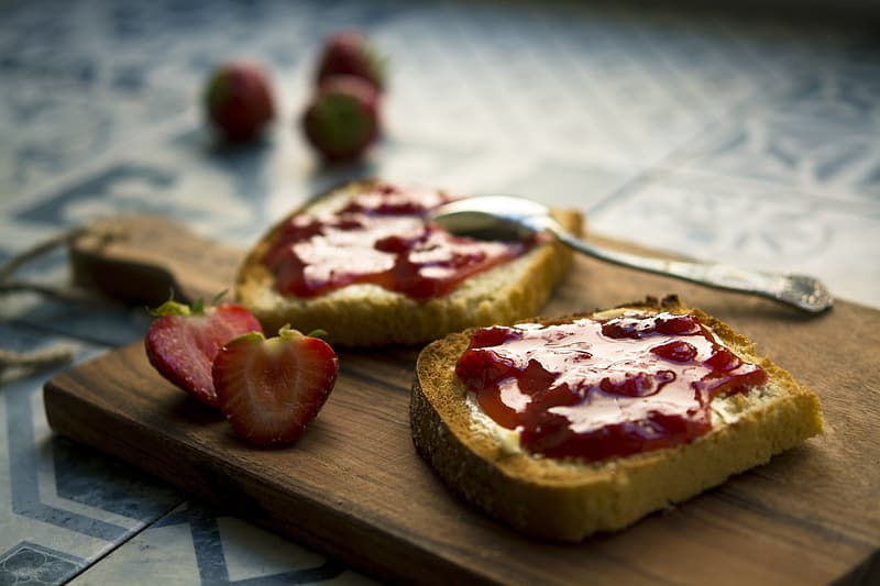 Shallow focus photography of loaf bread with strawberry jam on brown wooden chopping board