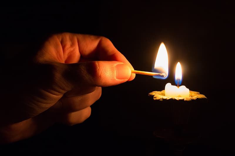 Person lighted candle using match stick