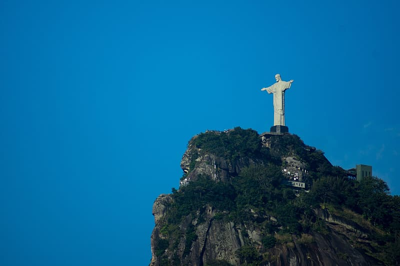 White cross on top of mountain during daytime