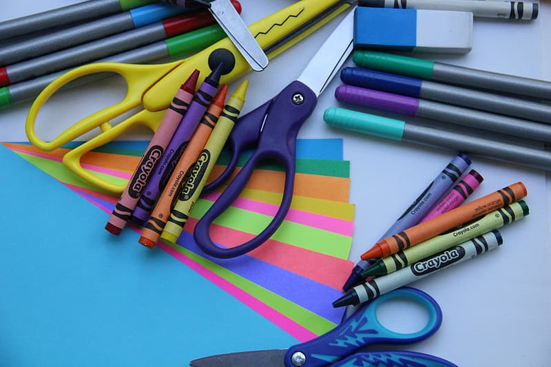Assorted-color Crayola crayons on table with scissors