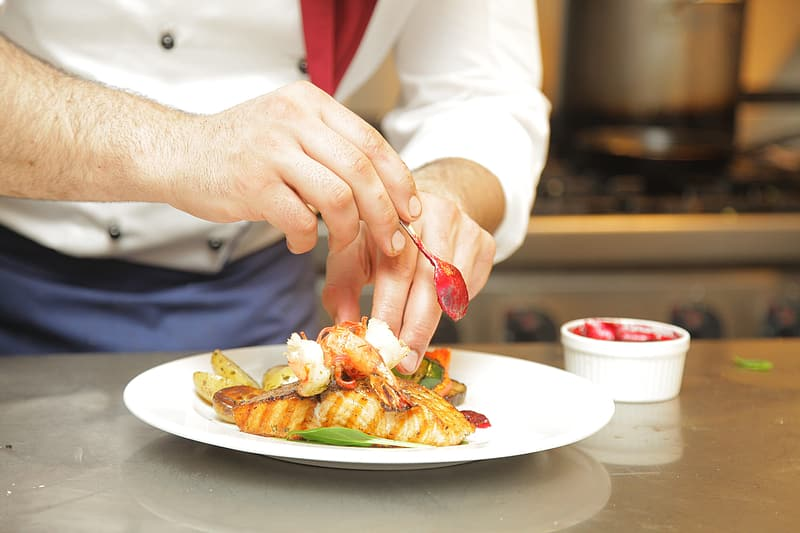 Chef arranging food dish on white ceramic plate