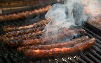 Grilled sausages on gray grill