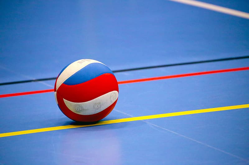 White blue and red volleyball on blue and yellow court