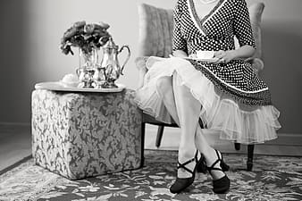 Grayscale picture of woman sitting next to end table