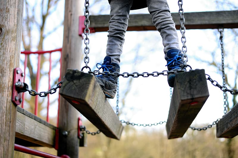 Person in black pants and black boots on brown wooden swing