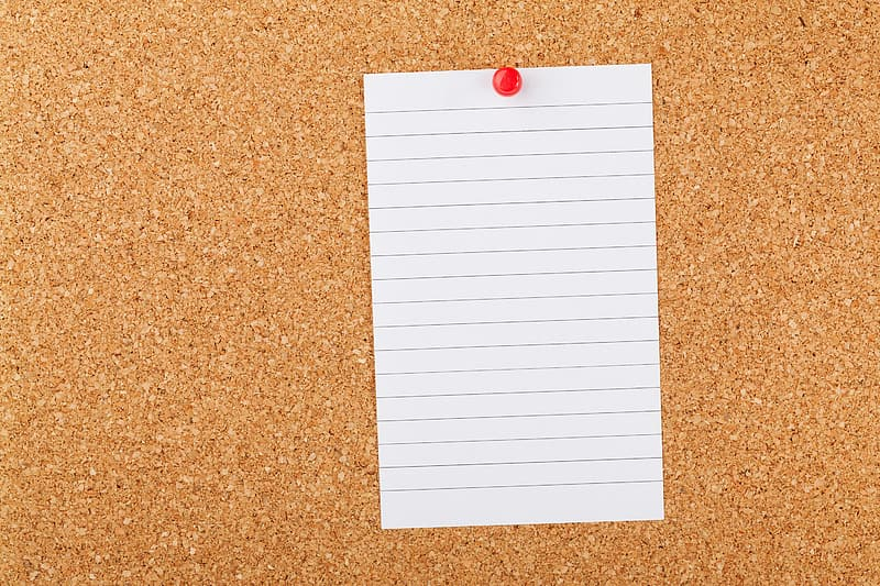 White page of notepad and brown cork board