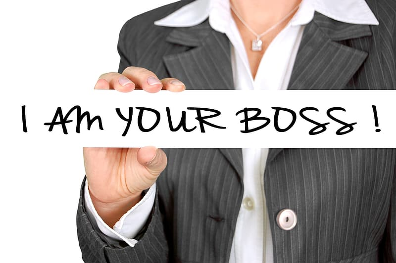 Woman wearing grey blazer holding i am your boss! sign