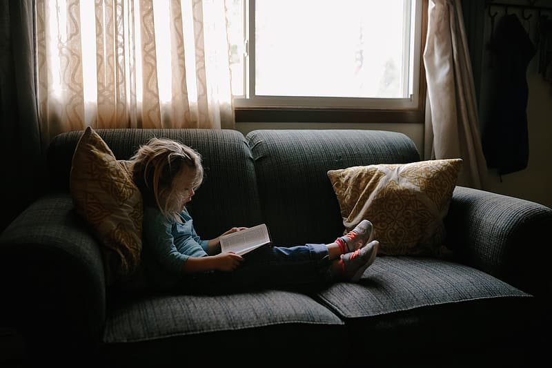 Child sitting on couch infront of window