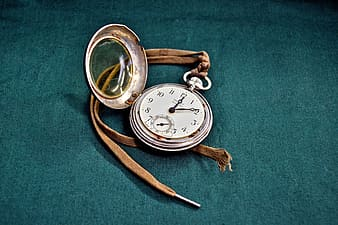 Round gray pocket watch with strap on gray textile