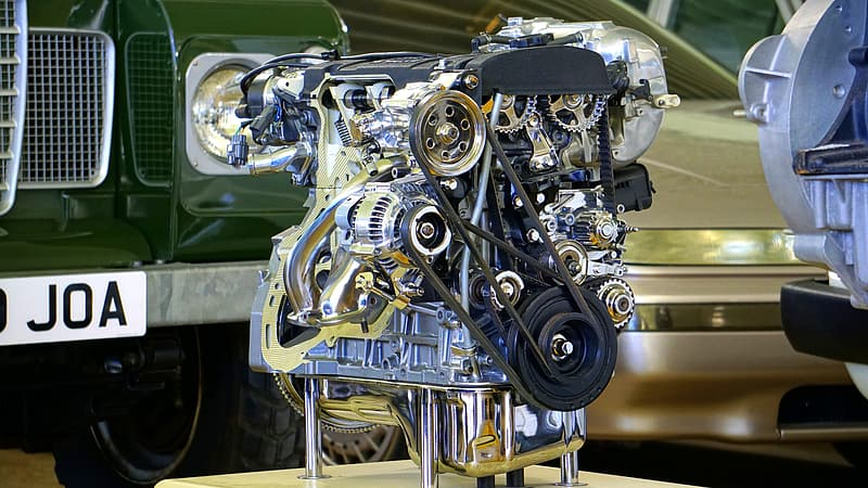 Silver vehicle engine beside green vehicle