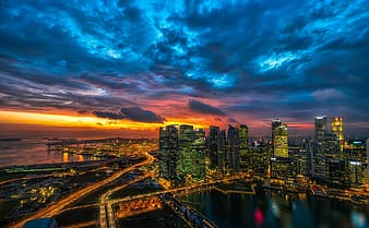 City skyline under cloudy sky during night time