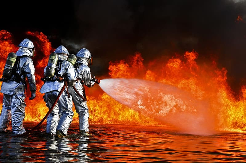 Three firefighters pointing water hose on flame