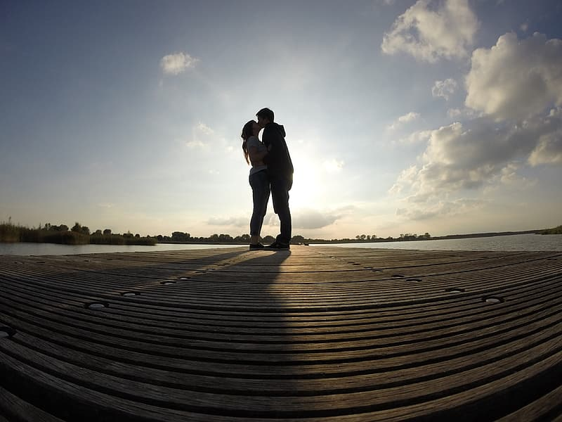 Silhouette of kissing man and woman fish-eye photography