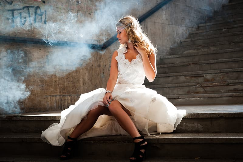 Woman wearing white dress sitting on stair case