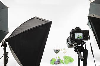 Photoshoot of wine glasses filled with green and purple grape wines with grapes