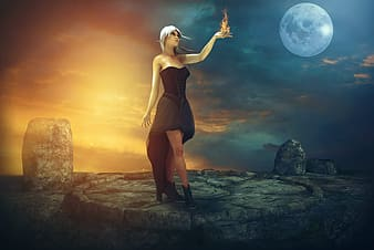 Woman in black spaghetti strap dress standing on rock during night time