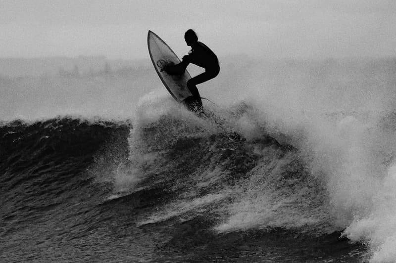 Grayscale photo of man riding surfboard