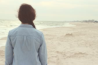 Woman wearing blue collared shirt standing near seashore