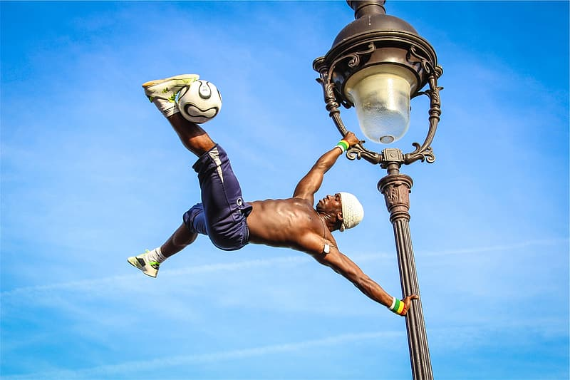Man wearing black shorts and pair of yellow sneakers holding on gray metal light post