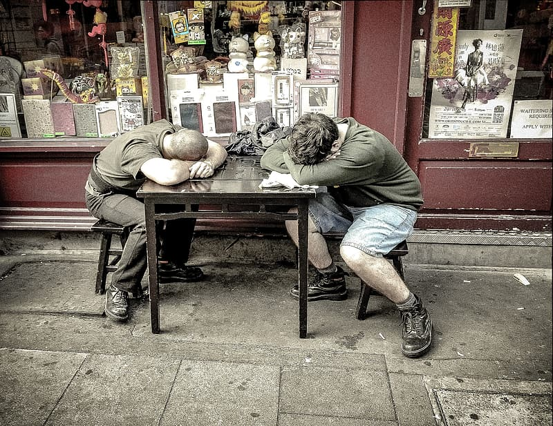 Two men sleeping on table outside store
