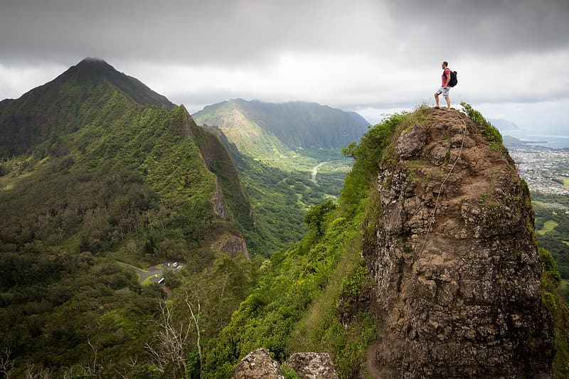 Photography of man wearing backpack standing on cliff