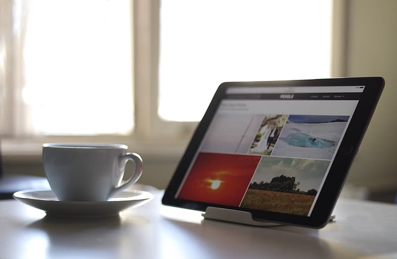 Tablet computer on stand beside ceramic cup