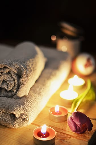 Folded bath towel beside four lighted tealights on top of beige wooden table