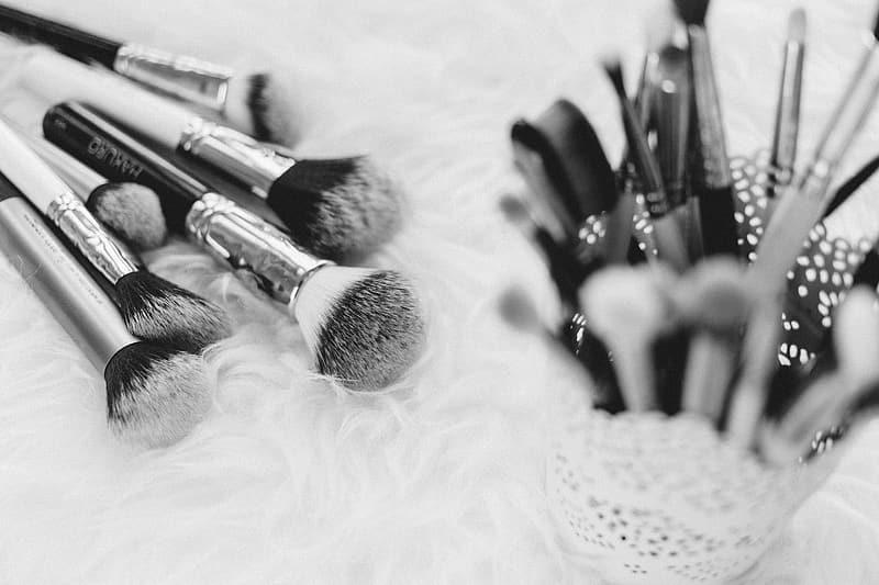 Gray and black handle makeup brushes on white textile