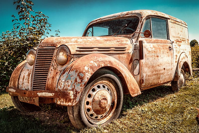Photo of rusty vintage white car on green grass