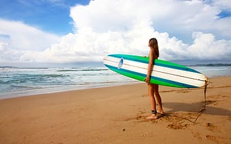 Woman in blue and white bikini holding white and green surfboard standing on beach during daytime