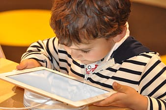 Boy in white and black striped shirt holding white tablet computer