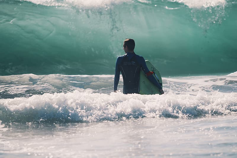 Man in blue wet suit carrying a surf board