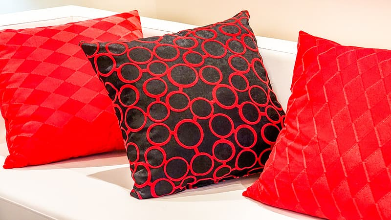 Three red throw pillows on white sofa