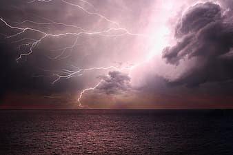 Lightning strike on the ocean during sunset