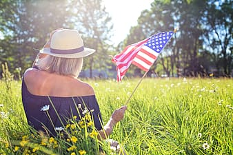 Woman holding U.S.A flag sitting on green grass field during daytime