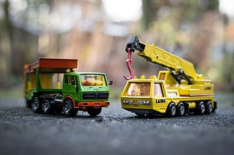 Two yellow and green truck miniatures