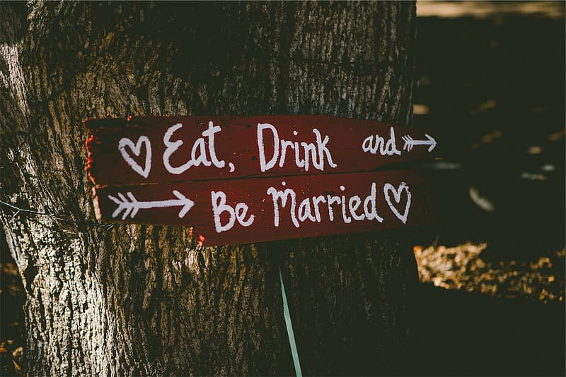 Two brown-and-white eat, drink, and be married-printed wooden board signage leaning on tree trunk