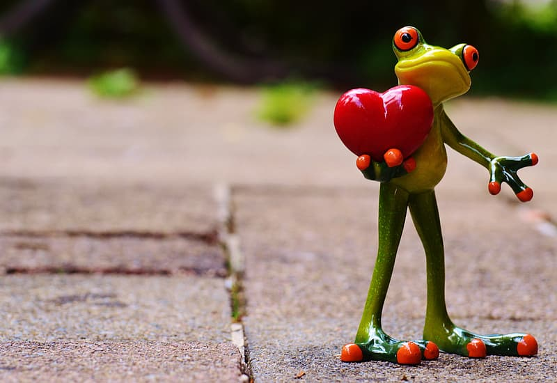 Green frog holding red heart ceramic figurine