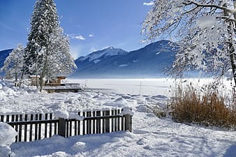 Brown wooden fence on snow covered ground near snow covered mountain during daytime