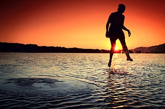 Person jumping on beach during golden hour