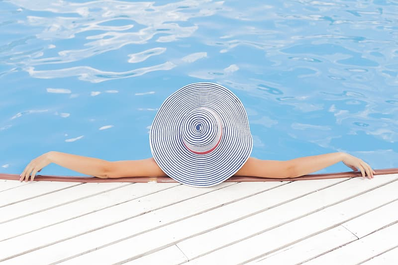 Woman in white and black stripe sun hat on swimming pool