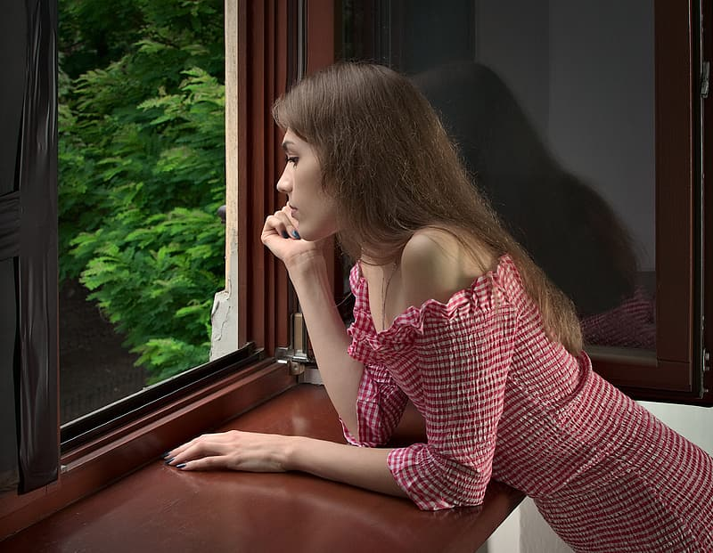 Girl in red and white stripe dress sitting on window