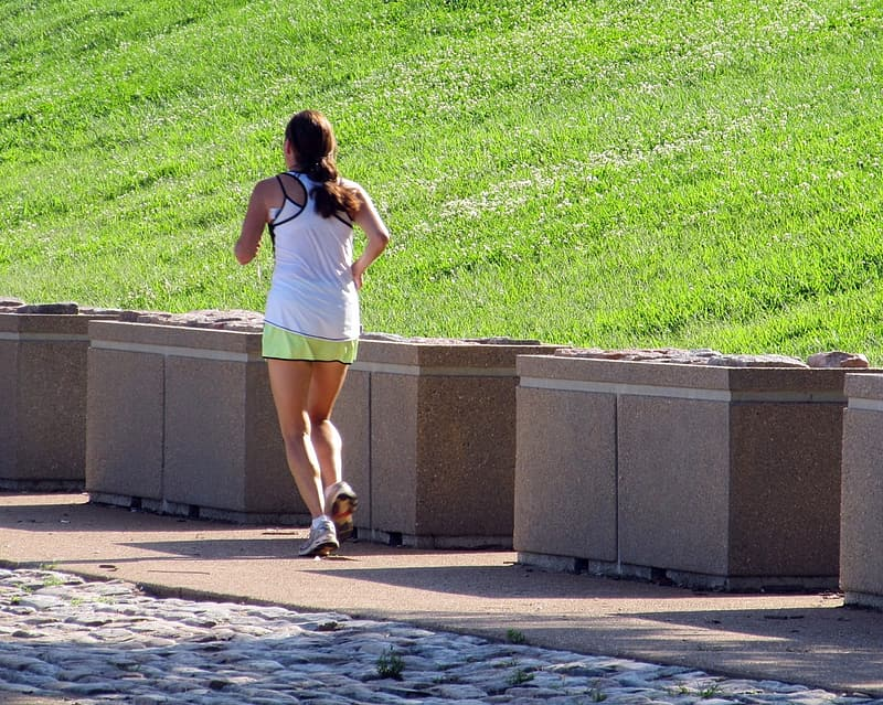 Woman running near brown concrete obstacles