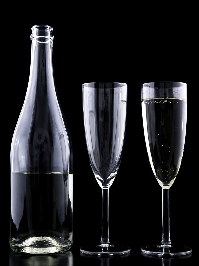 Two clear drinking glasses beside clear glass bottle