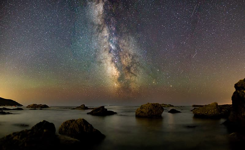 Brown rock formation on body of water under starry night