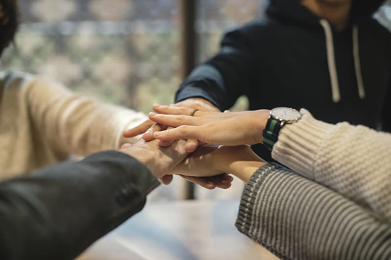 Four people placing hands together
