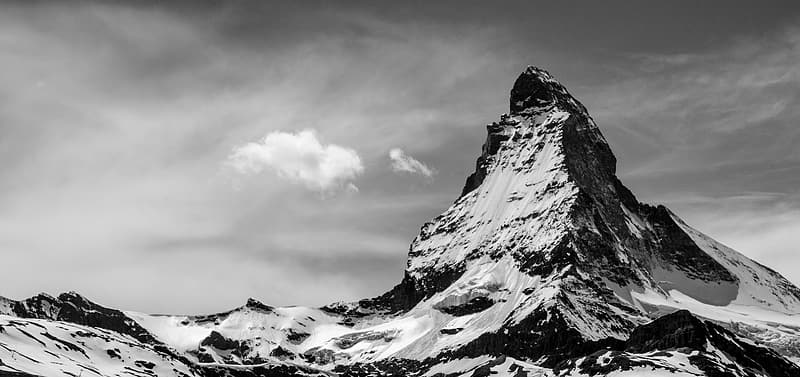Grayscale photography of snow capped mountain under cloudy sky